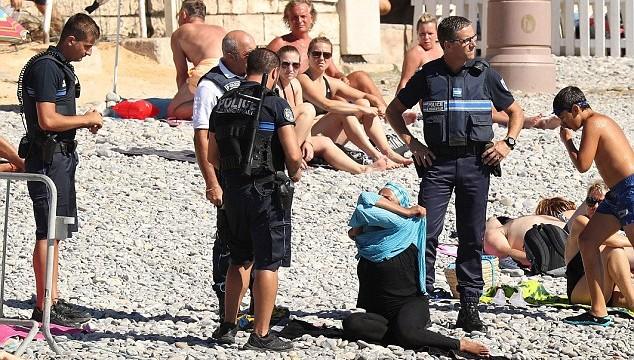 """VIDEO: """"Novelc to!"""" Bruņoti policisti Nicas pludmalē musulmaņu sievietei pieprasa novilkt burkini – pilno peldkostīmu. Un izraksta soda kvīti!"""